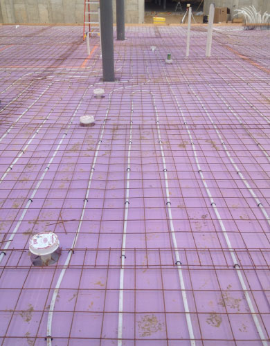 Radiant heating system being layed out before concrete is poured over to seal it within the structures floor.